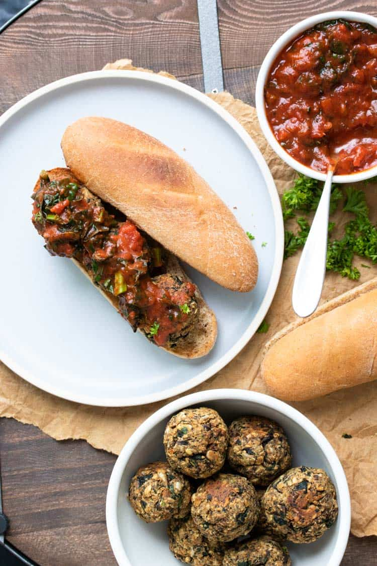 Open faced vegan meatball sub next to bowls of marinara and vegan meatballs