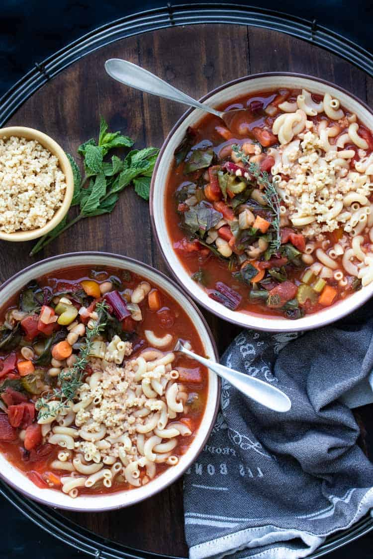 Two bowls of vegetable minestrone soup on a wooden tray