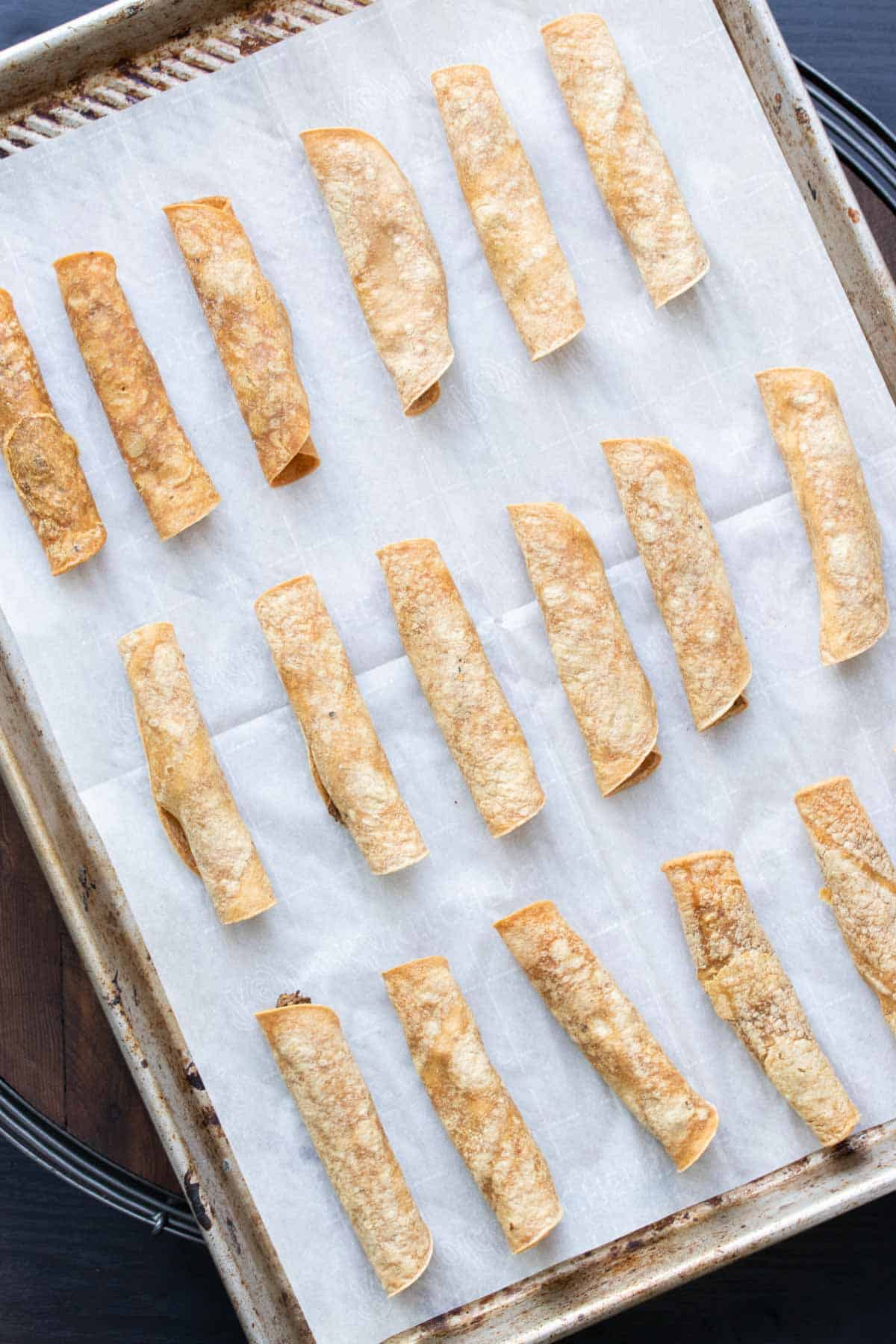 Baked taquitos on a baking sheet lined with parchment paper.