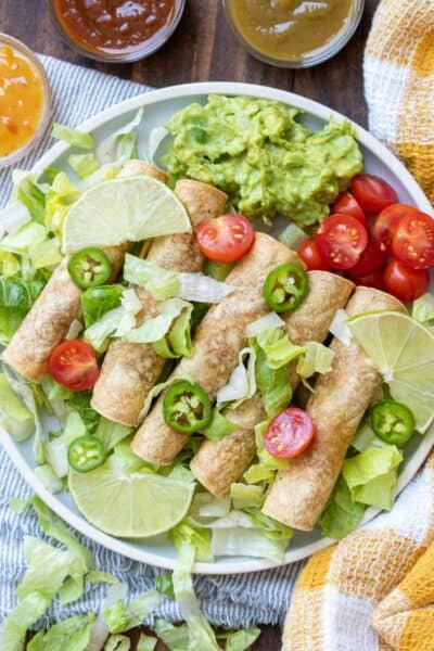 Taquitos on a white plate with all the fixings surrounded by bowls of sauces