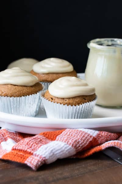 Pumpkin cupcakes with white frosting on a white plate