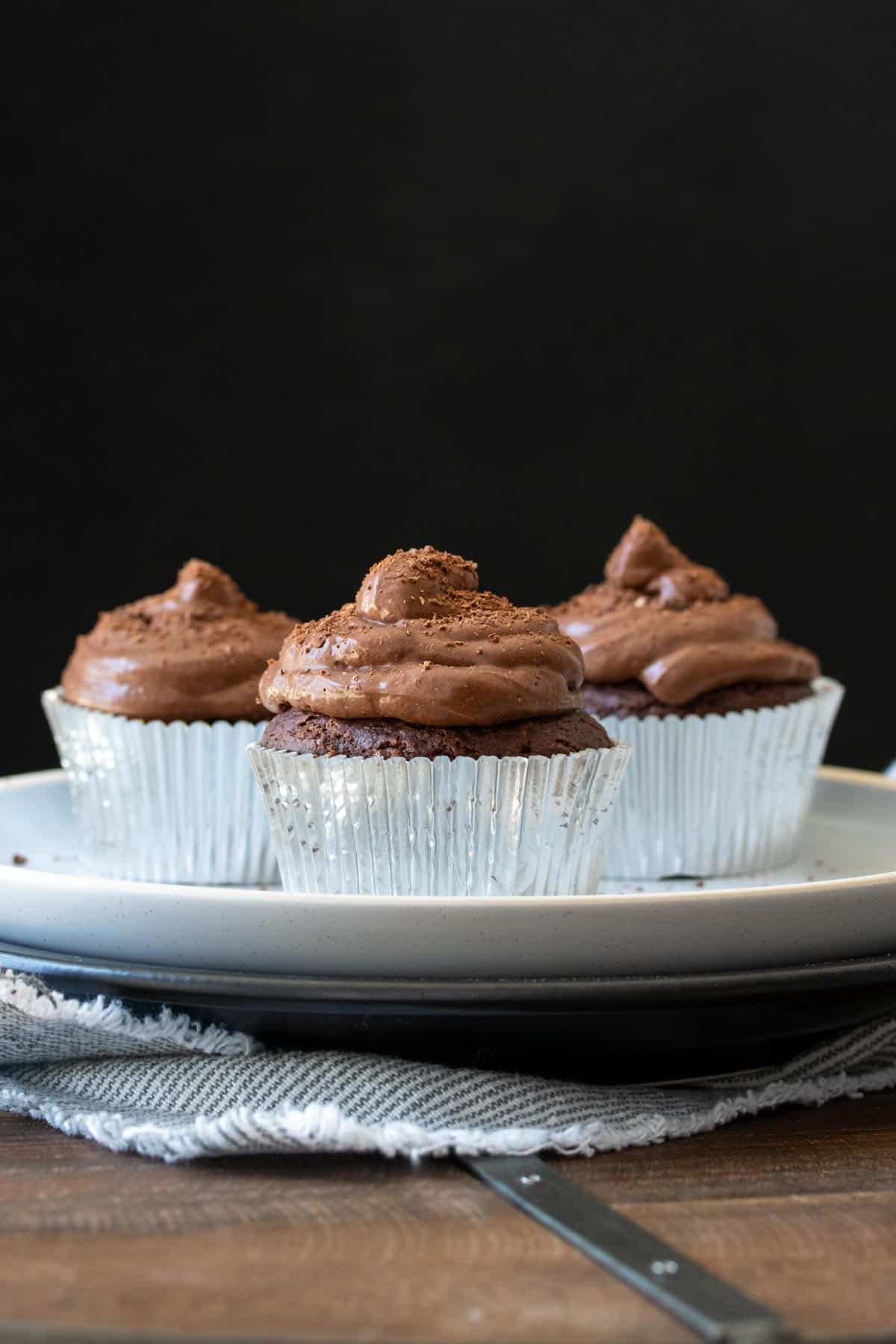 Three chocolate cupcakes with silver liners on a white plate