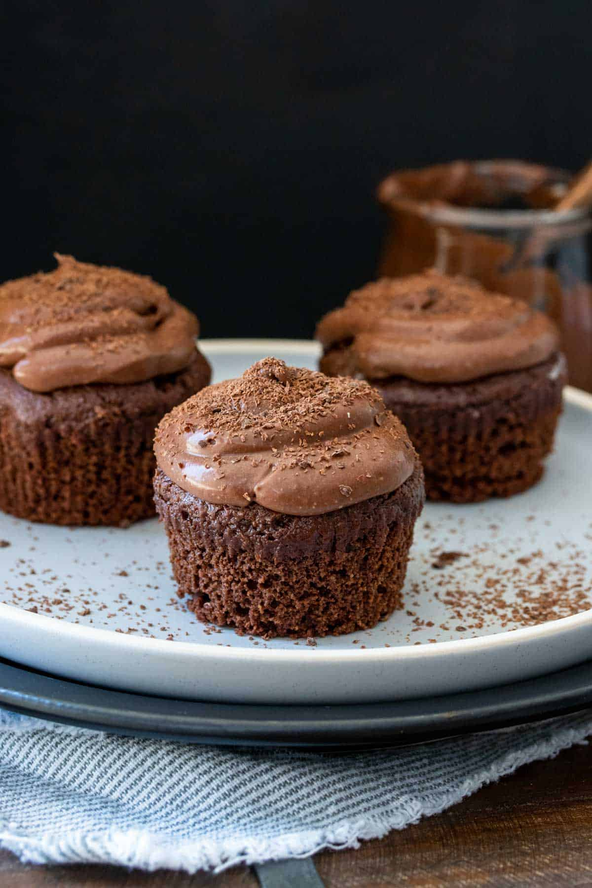 Chocolate cupcakes with chocolate frosting and no liners on a white plate