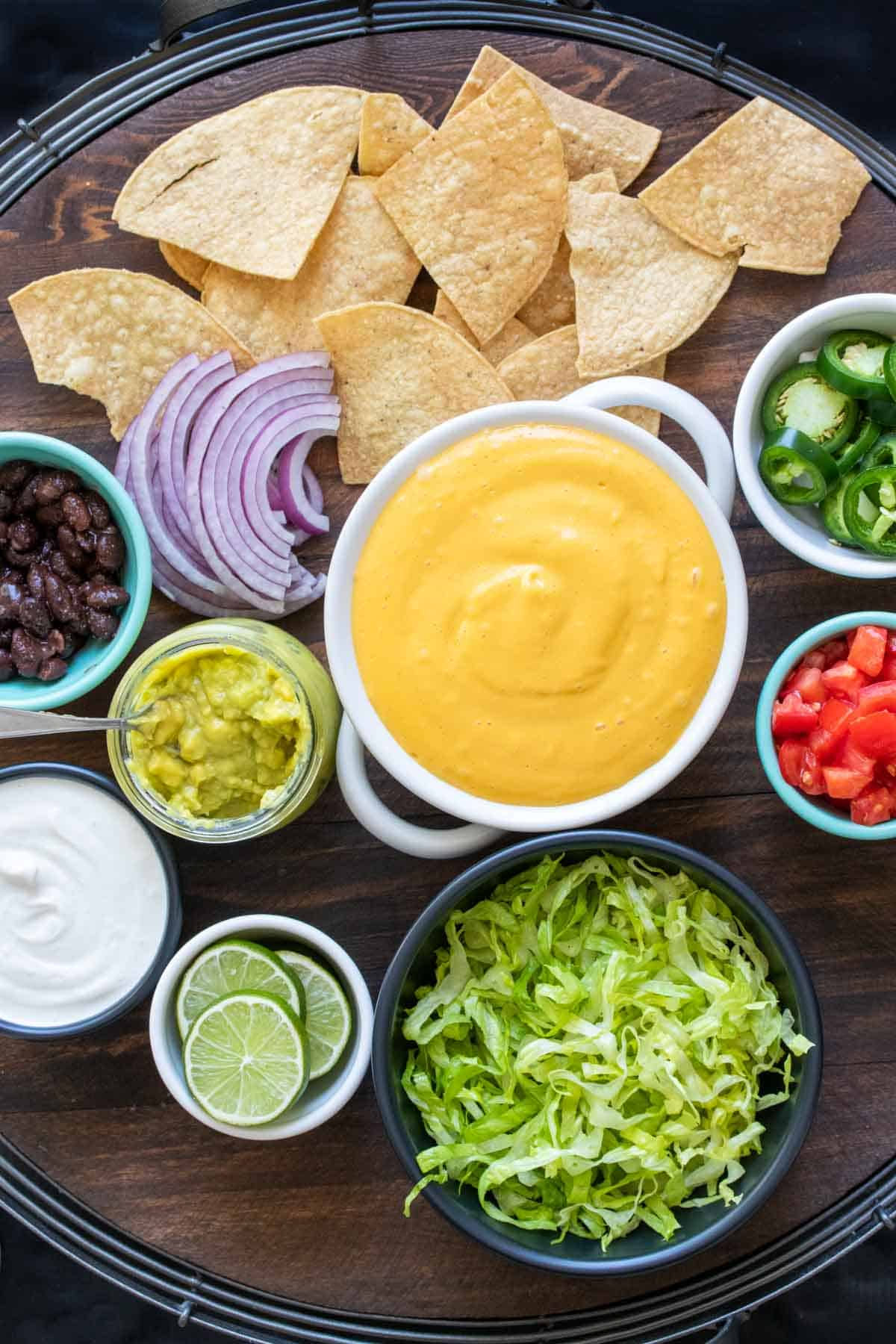 Ingredients for nachos in bowls on a wooden tray