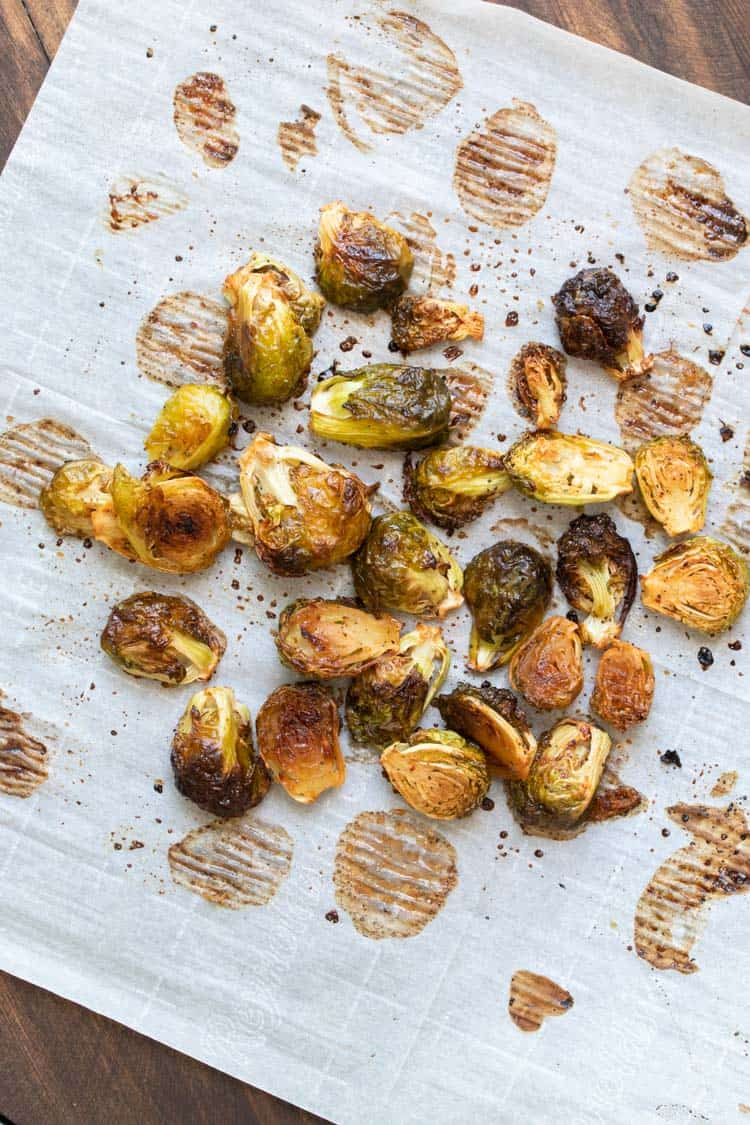 Roasted Brussels sprouts on a piece of parchment paper.