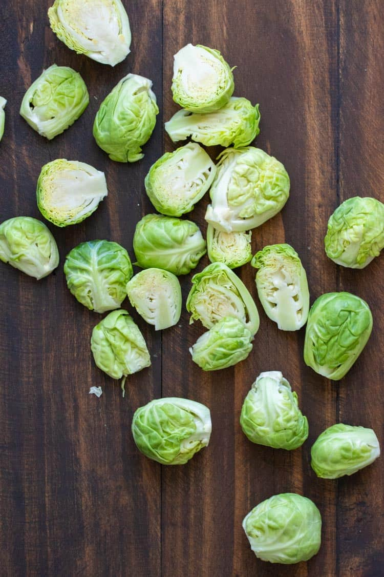 Cleaned and cut in half Brussels sprouts on a wooden table.
