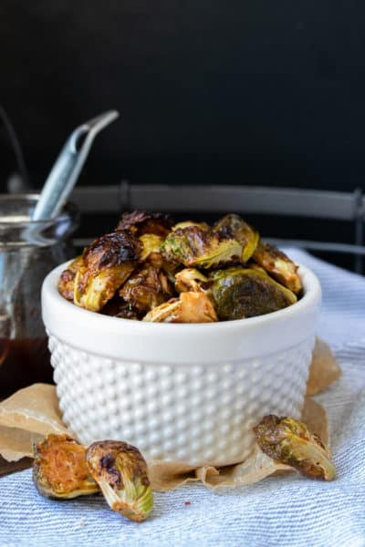 White bowl on a grey and white striped towel filled with roasted Brussels sprouts