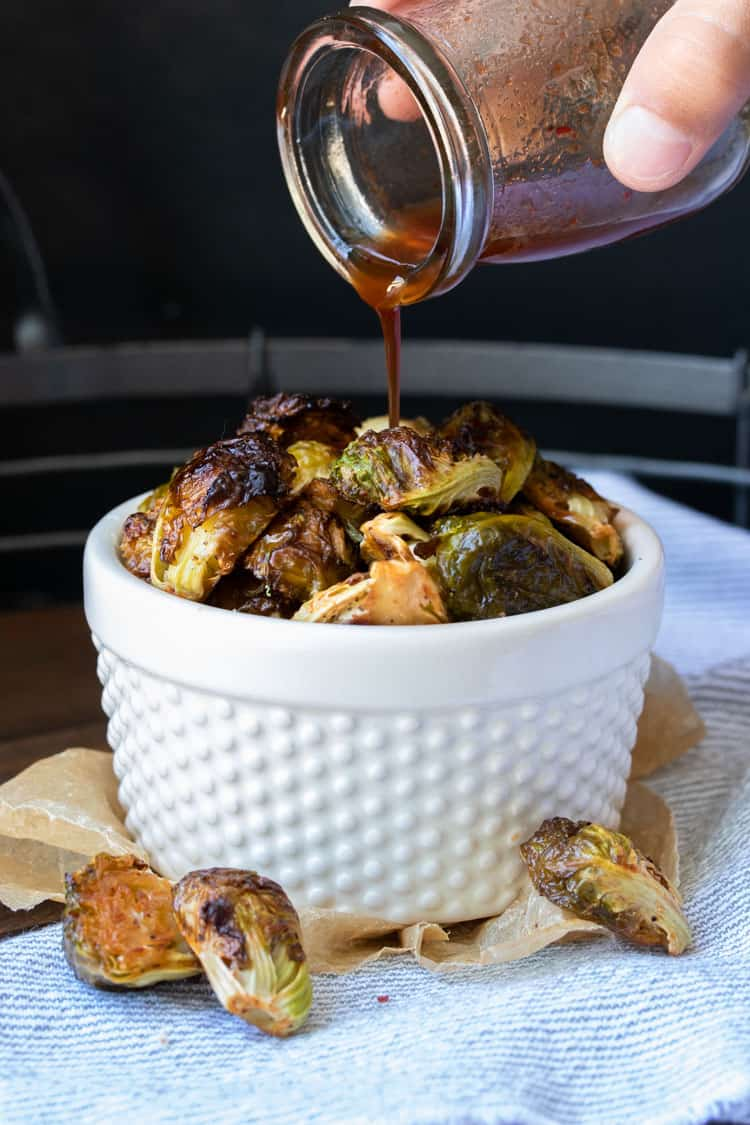 Hand pouring maple syrup sauce over a bowl of roasted Brussels sprouts