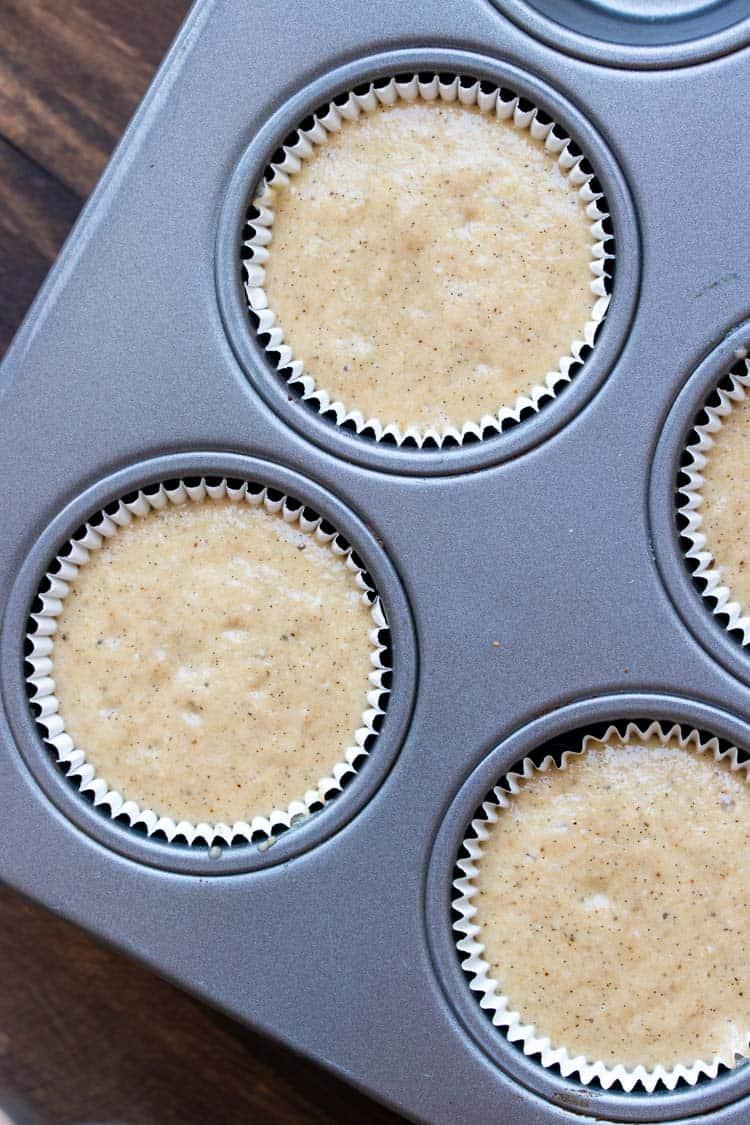 Vanilla cupcake batter in cupcake liners in a muffin pan