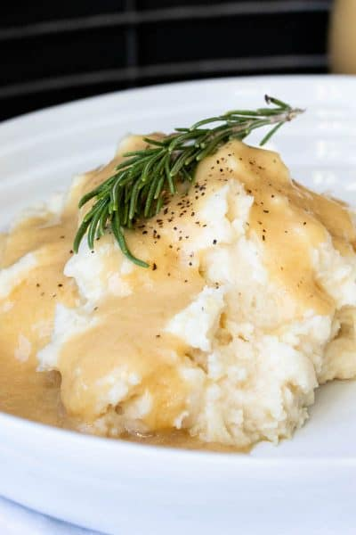 Rosemary sprig on a pile of mashed potatoes covered in gravy