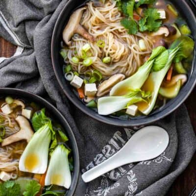 Two bowls of veggies and noodle soup on a wooden table