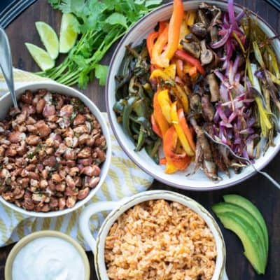 Bowls of different veggies, rice, beans and sour cream on a wooden tray
