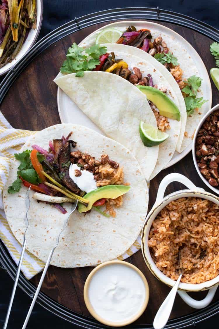 Tortillas filled with veggies, rice and beans on a wooden tray.