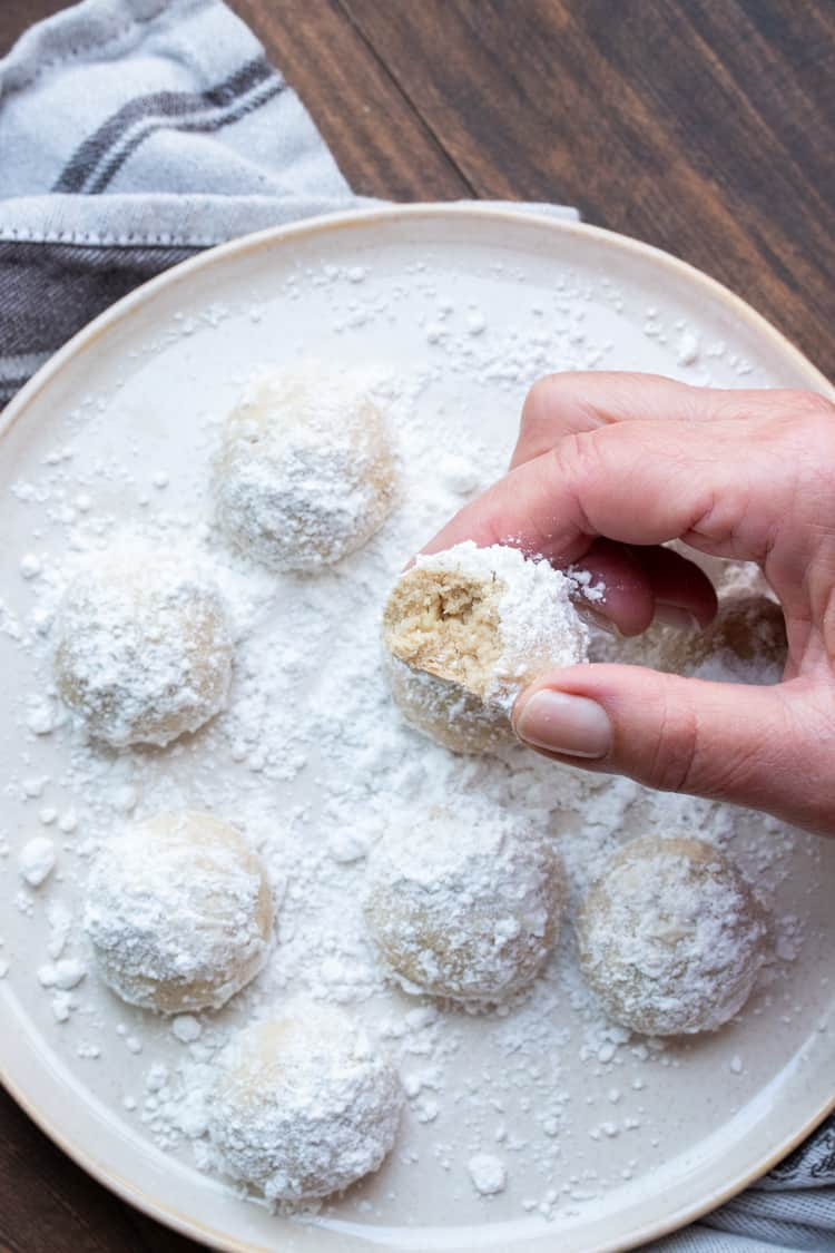 Hand holding a bitten powdered sugar covered butter cookie