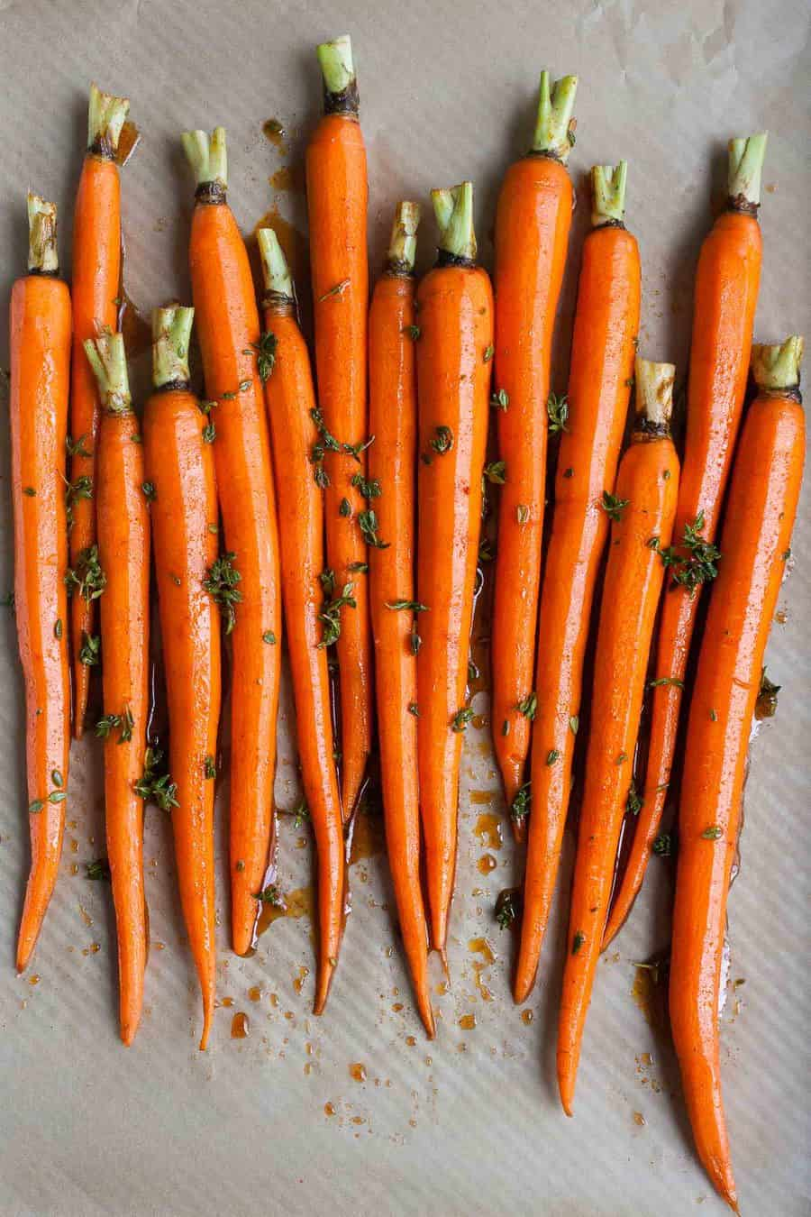Carrots being roasted on a baking sheet