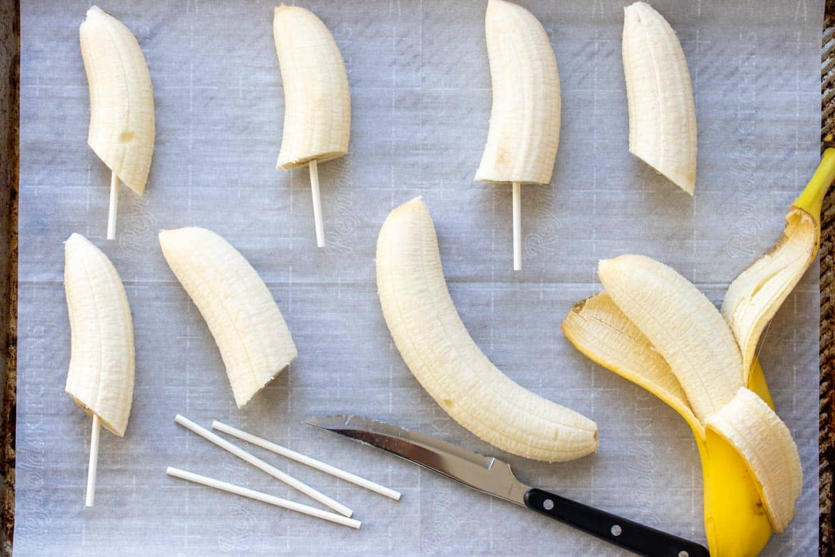Half cut bananas on sticks laying on parchment paper