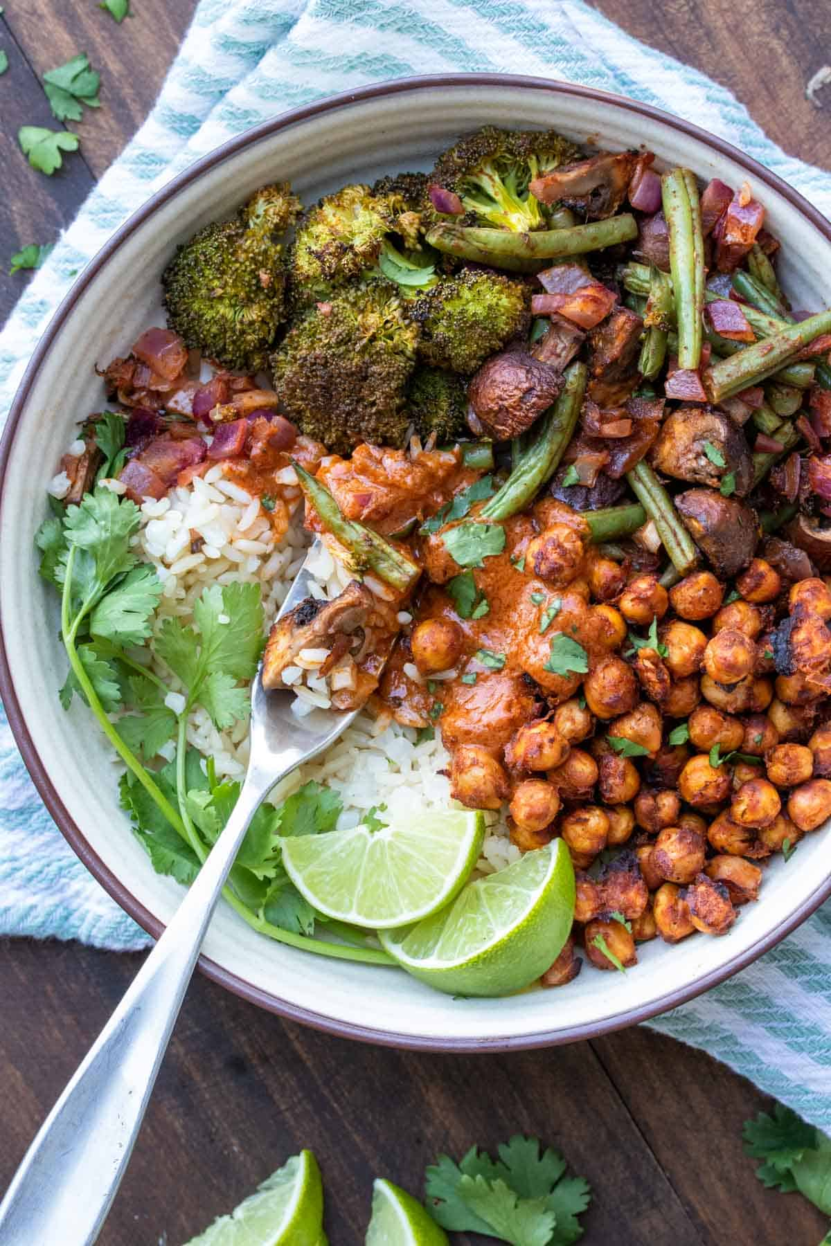 Fork getting a bite of rice with tikka masala sauce and roasted veggies and chickpeas