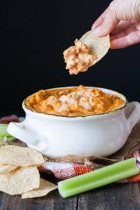 Hand using chip to take a bite from a bowl of baked buffalo dip