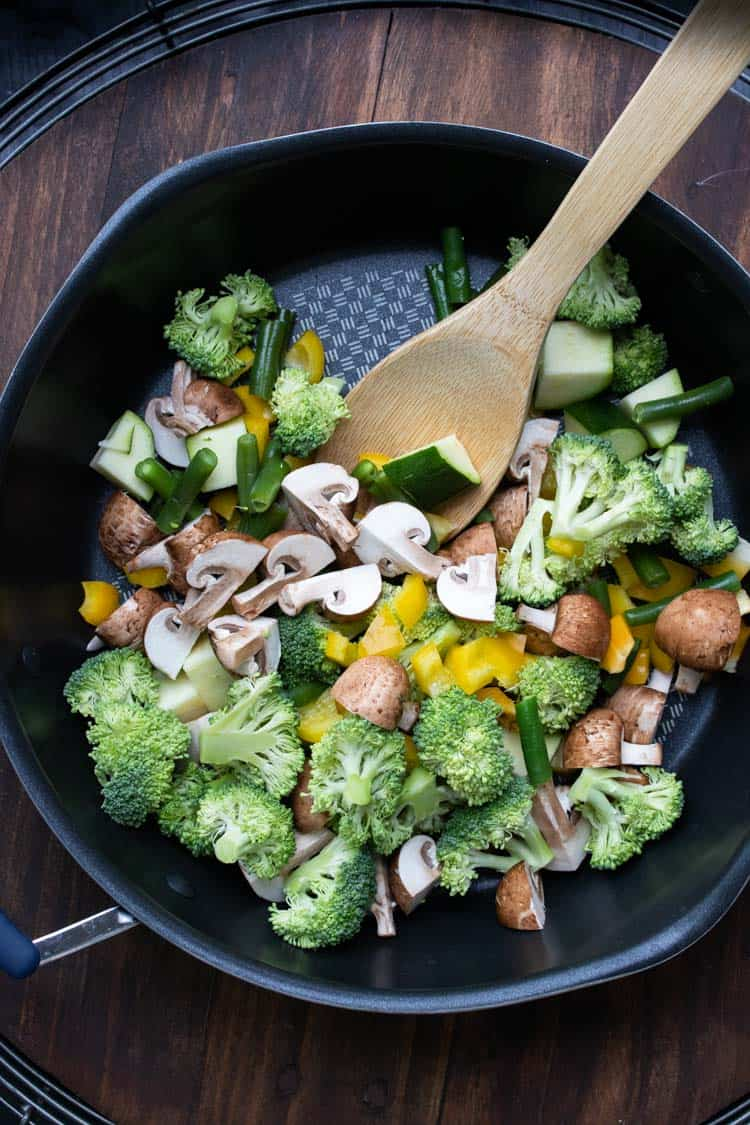 Wooden spoon mixing veggies in a pan