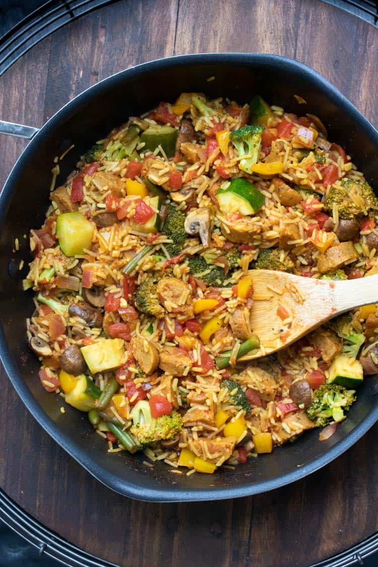 Wooden spoon mixing veggie paella mix in a pan