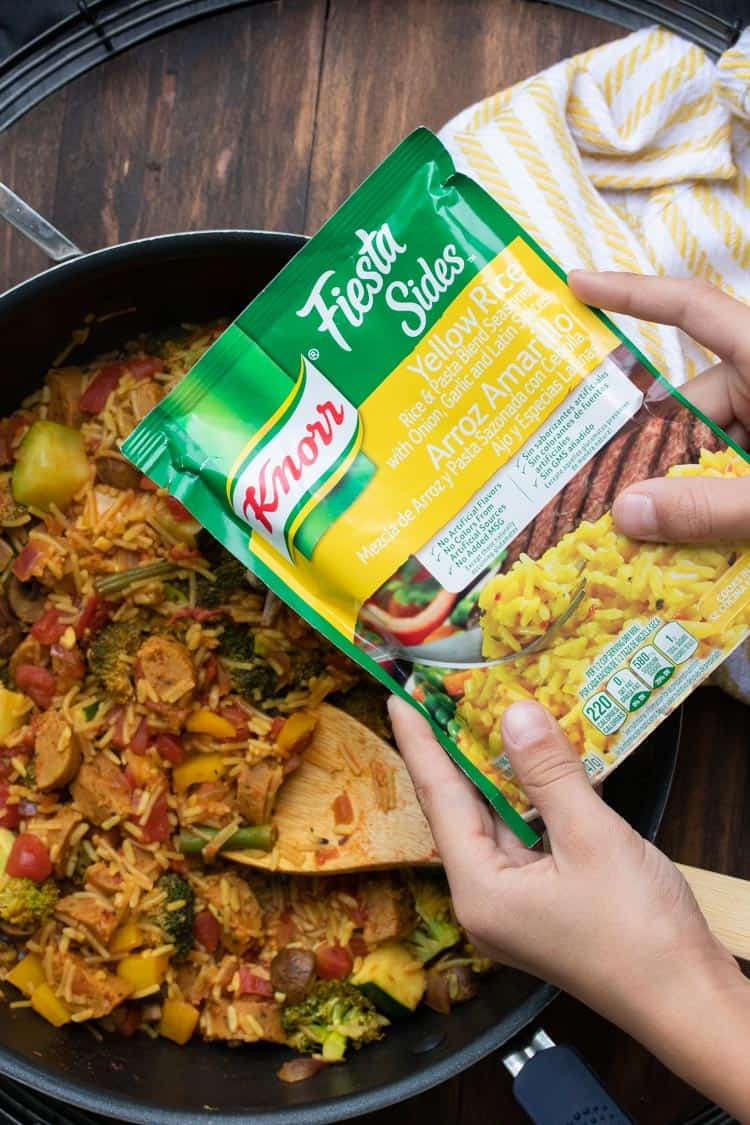 Hands holding package of dry rice mix over a pan of veggie paella