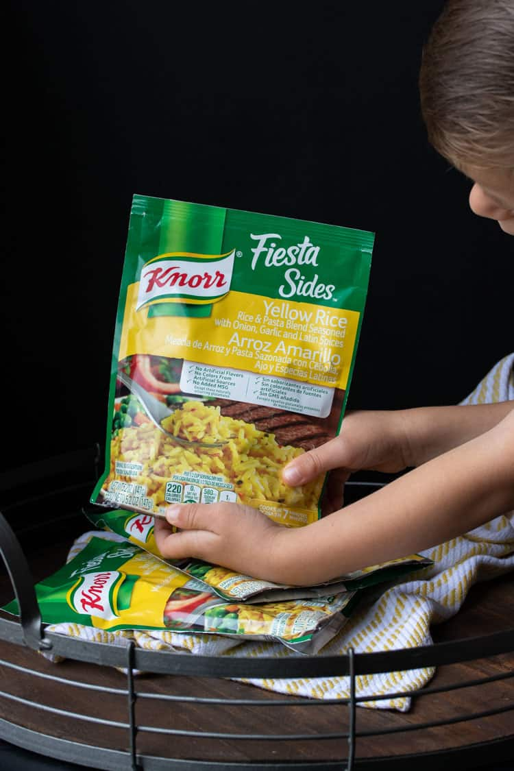 Child holding a package of Knorr brand rice mix