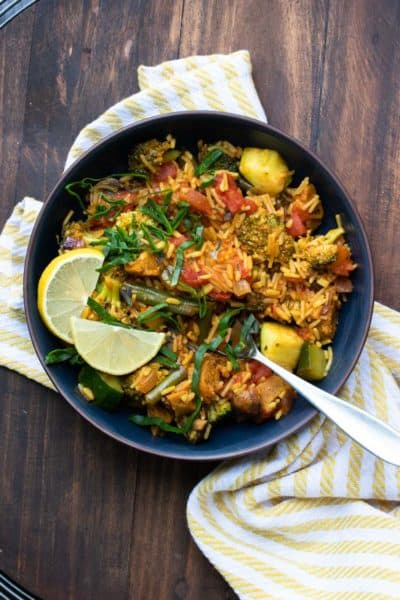 Black bowl of veggie paella topped with lemon slices and strips of greens