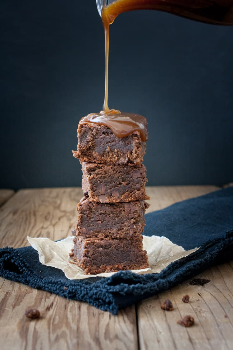 Caramel sauce pouring on a tower of brownies