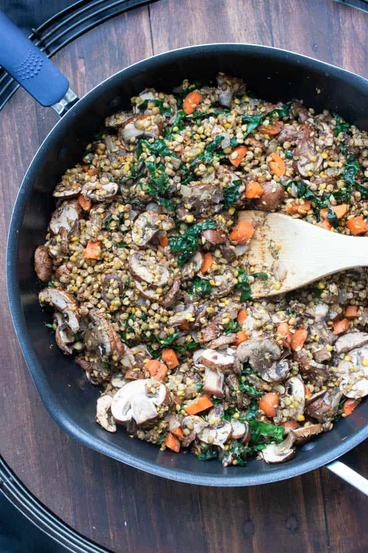 Wooden spoon sautéing lentils and veggies in a black pan
