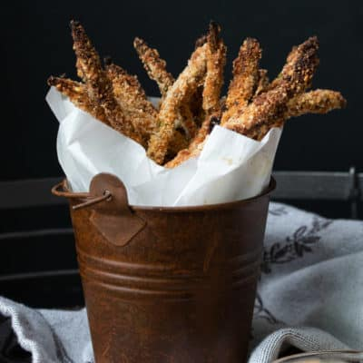 Crispy breaded asparagus fries wrapped in parchment in a brown bucket