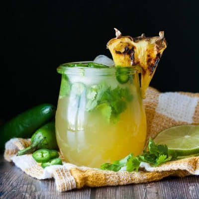 Grilled pineapple, jalapeño, cilantro margarita in a glass with a pineapple garnish