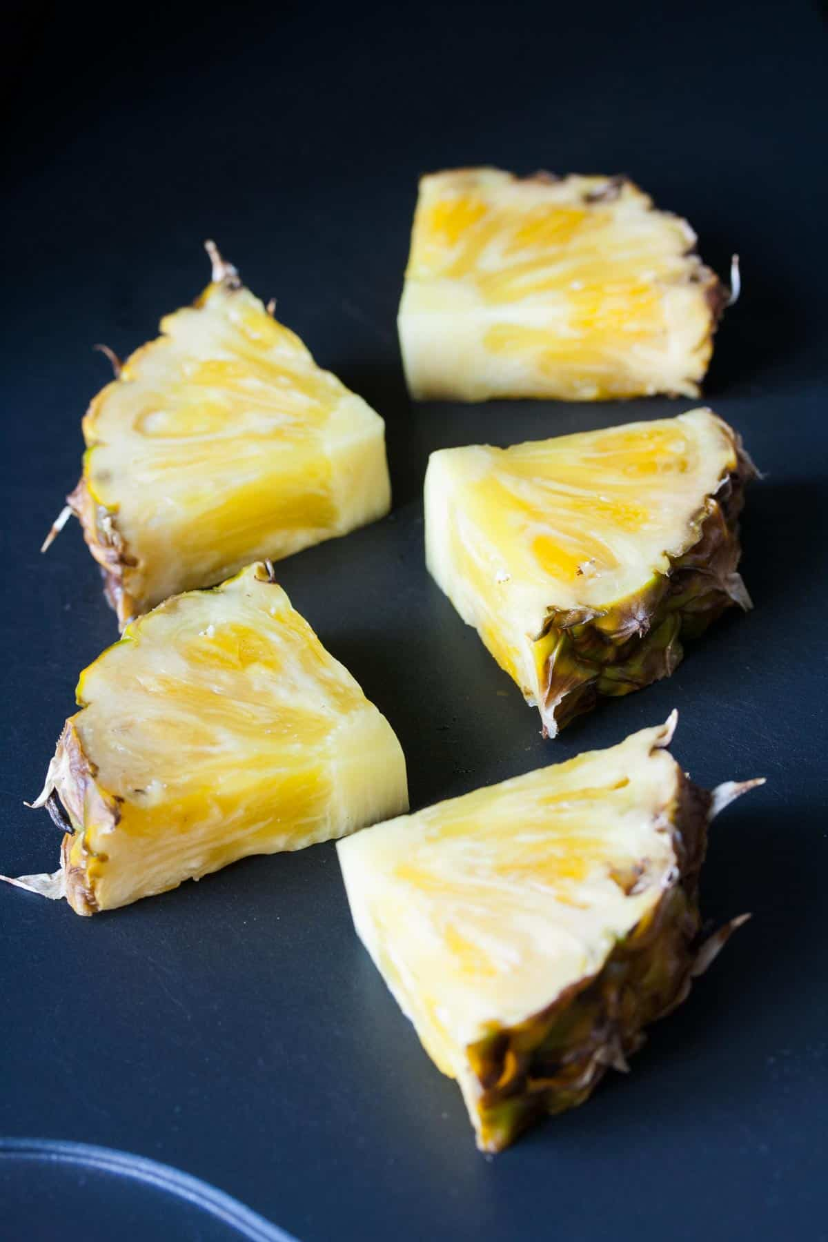 Slices of pineapple being grilled on a flat grill pan