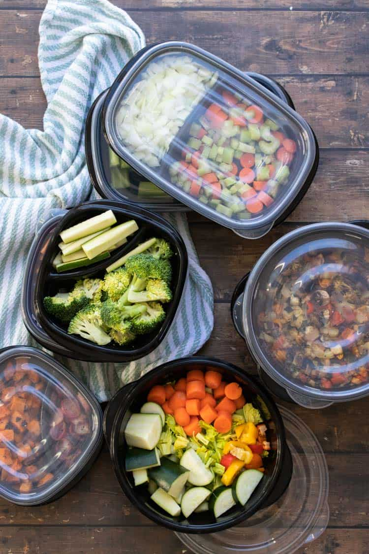 Black containers, some with lids on, filled with chopped veggies