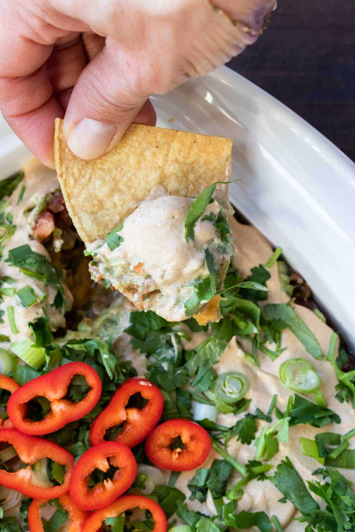 Hand dipping tortillas chip into a dish of 7 layer dip