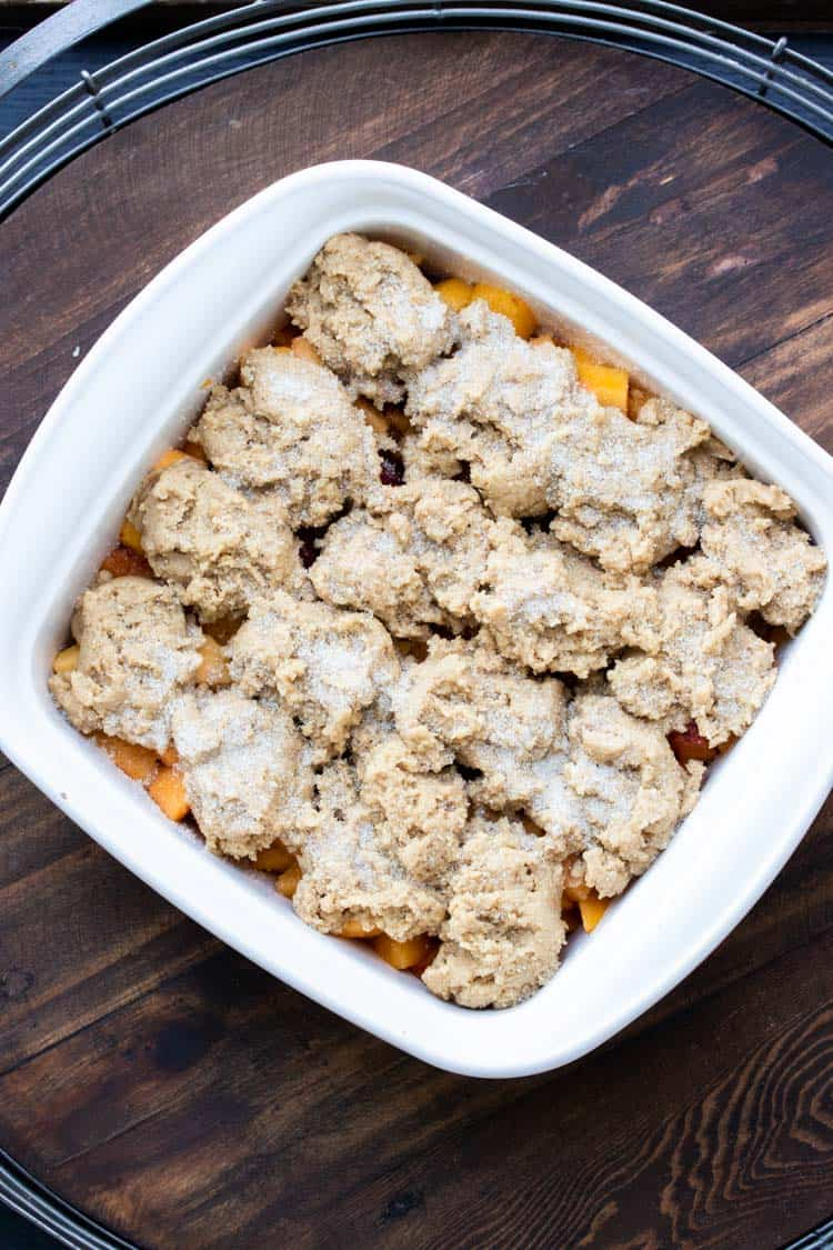 White baking dish filled with raw peach cobbler