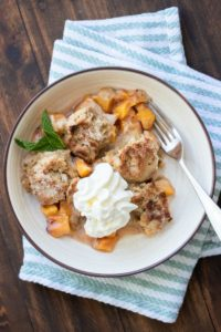 Peach cobbler with whipped cream in a cream bowl