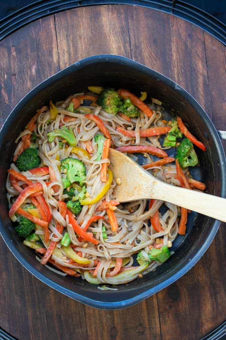 Wooden spoon mixing noodles and veggies in a pan