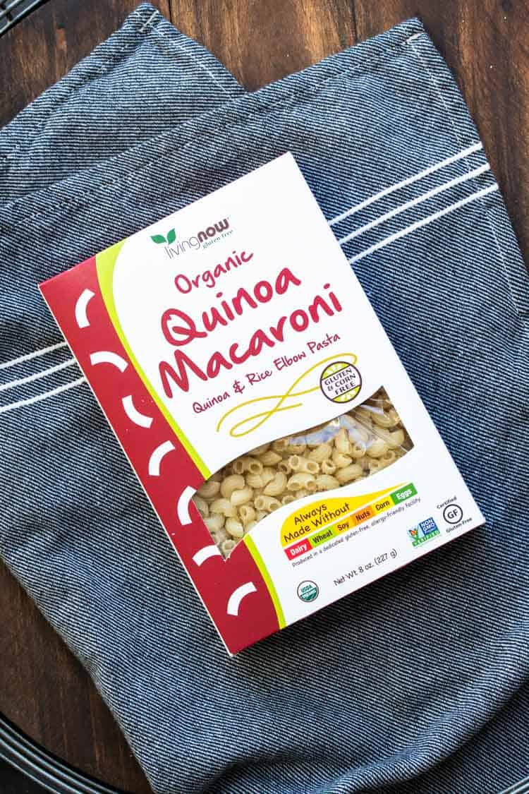Top view of box of quinoa macaroni pasta on a grey towel