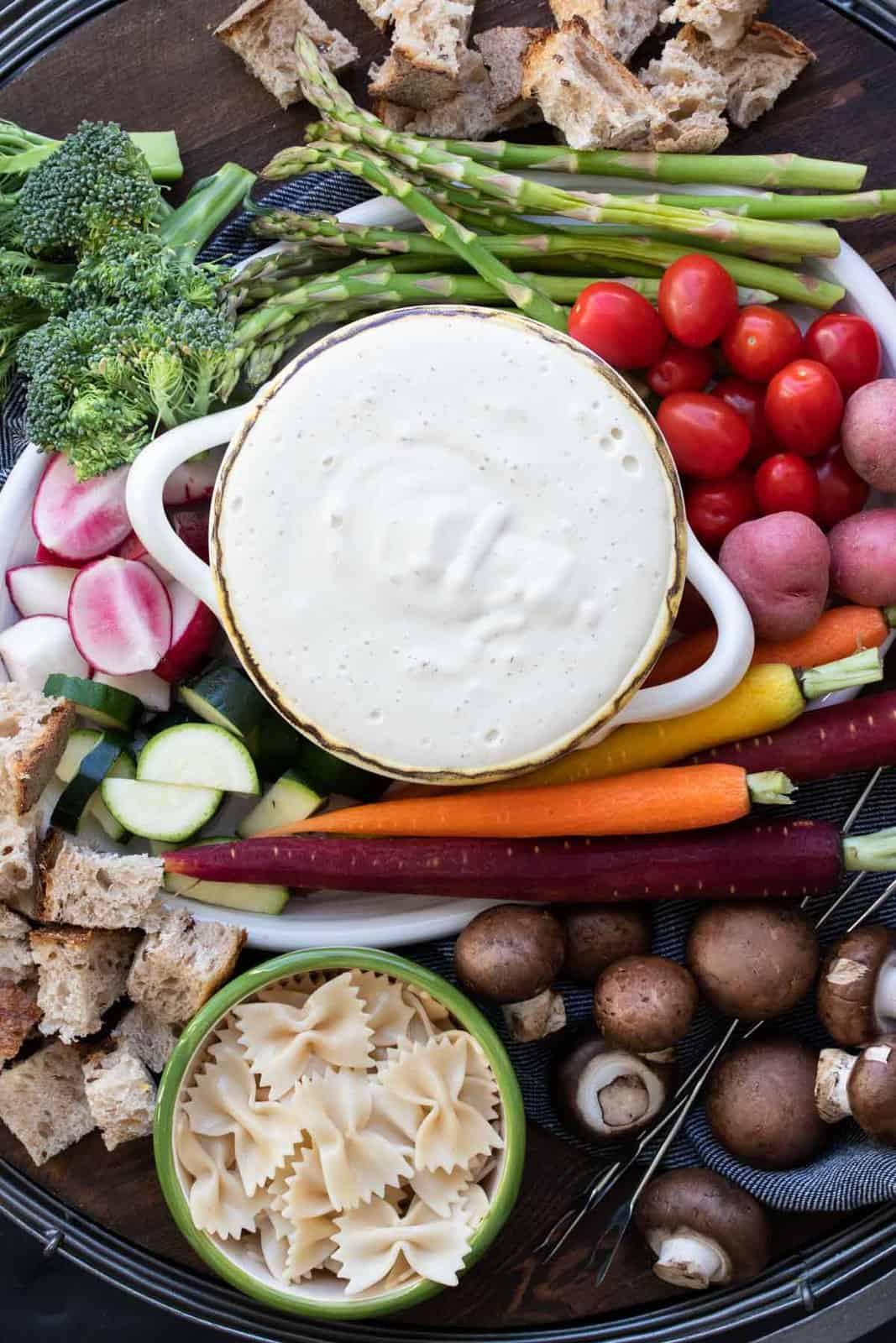 Bowl of white cheese fondue surrounded by veggies and bread