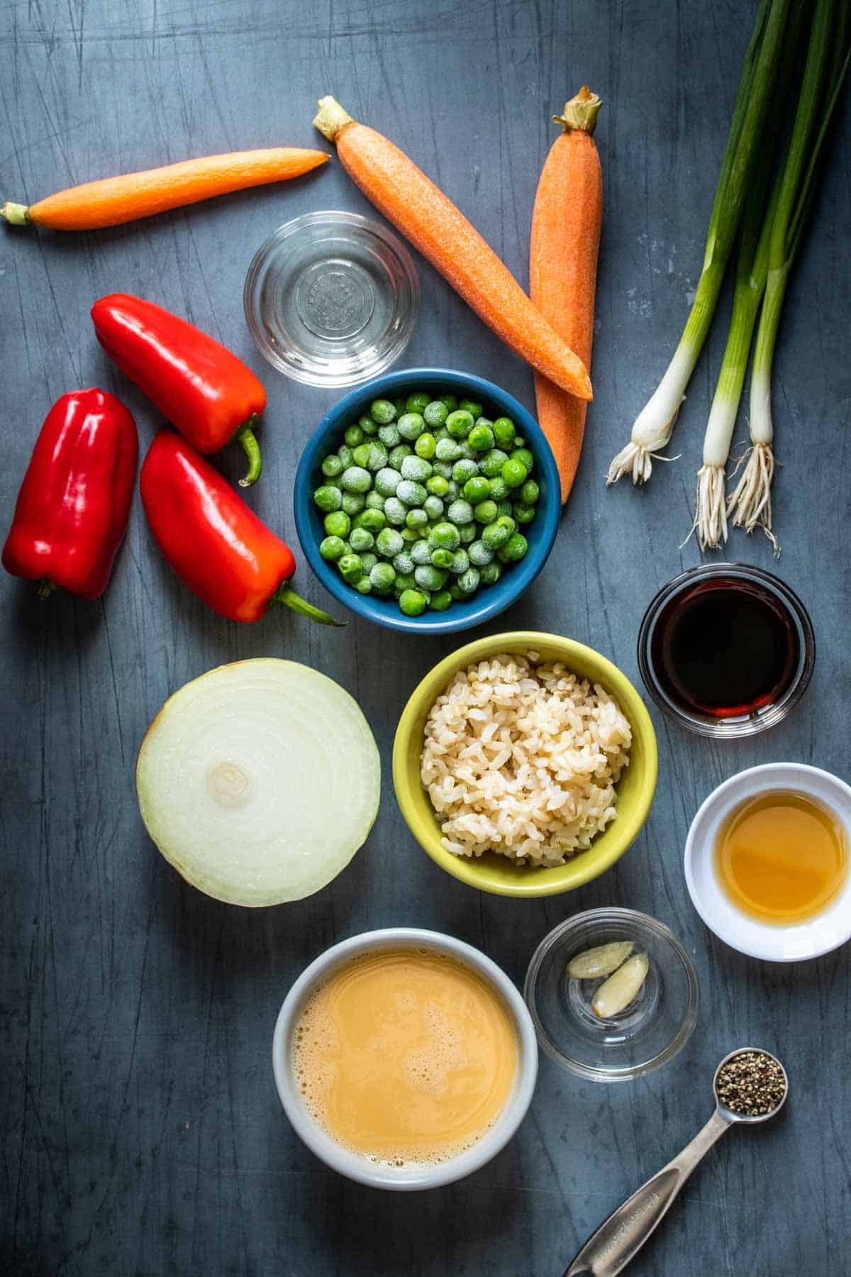 Bowls with ingredients for veggie fried rice on a wooden table