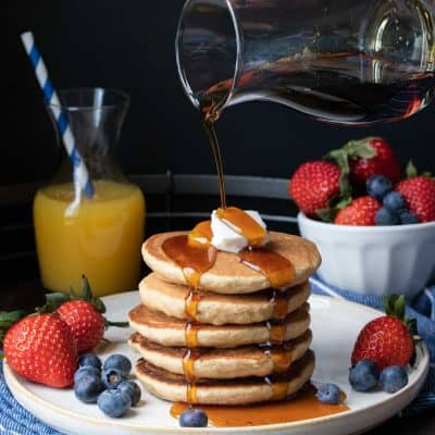 Maple syrup being poured over a stack of five pancakes on a white plate