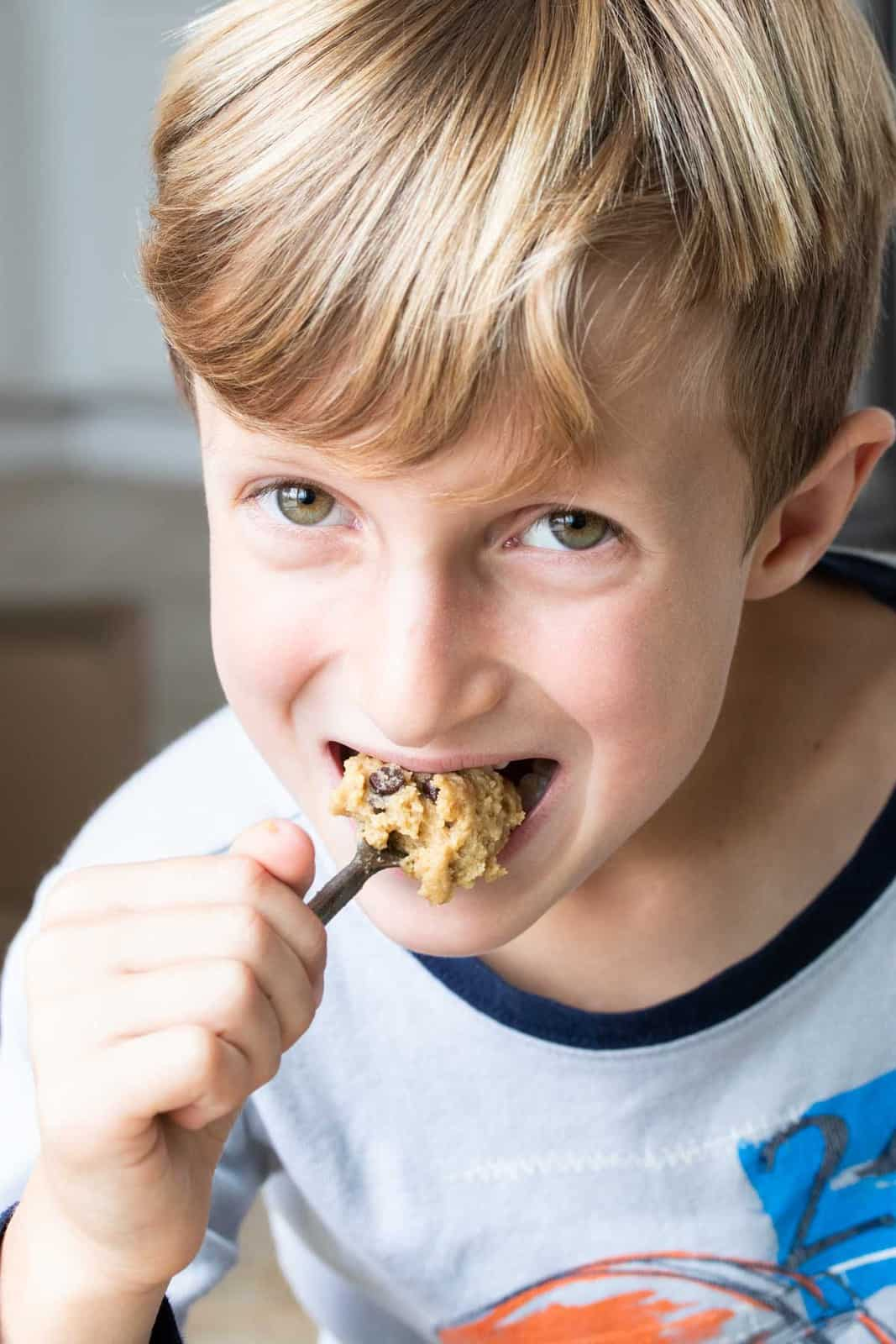 Boy eating raw chocolate chip cookie dough from a spoon