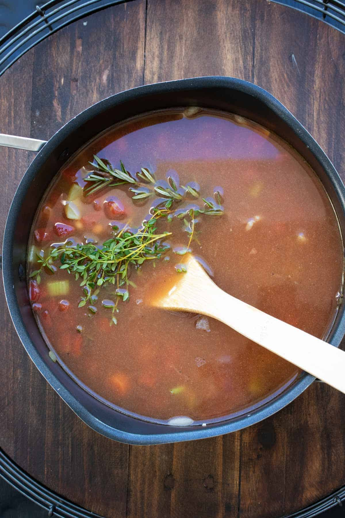 Veggie and bean soup in a pot with sprigs of rosemary and thyme on top