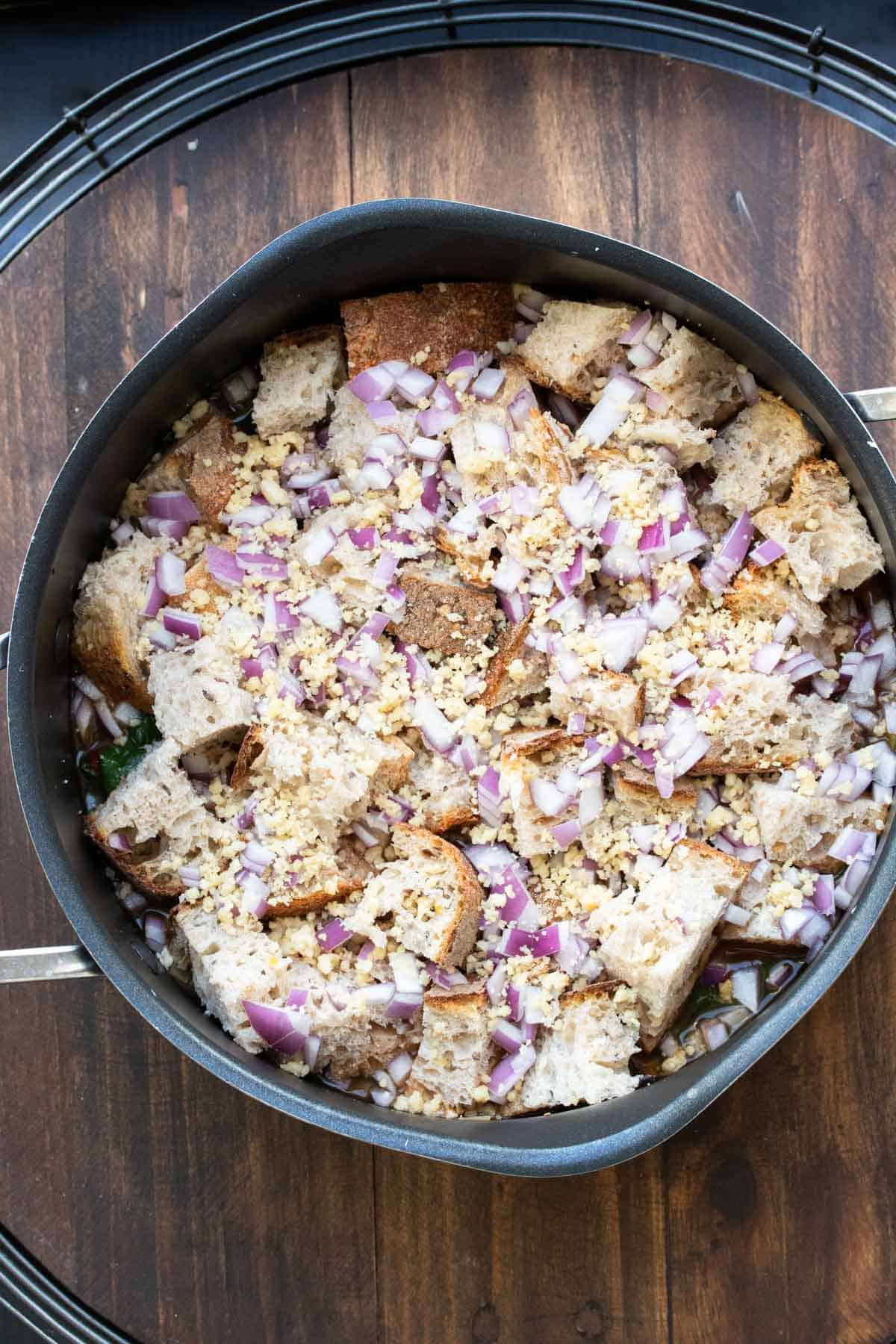 Bread cubes and chopped red onion on top of soup in a pot