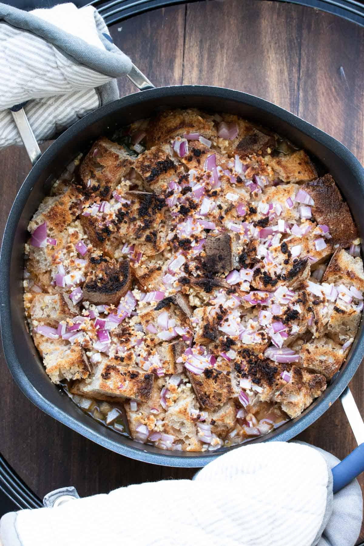 Crisp bread cubes with charred red onion on the top of soup in a pot