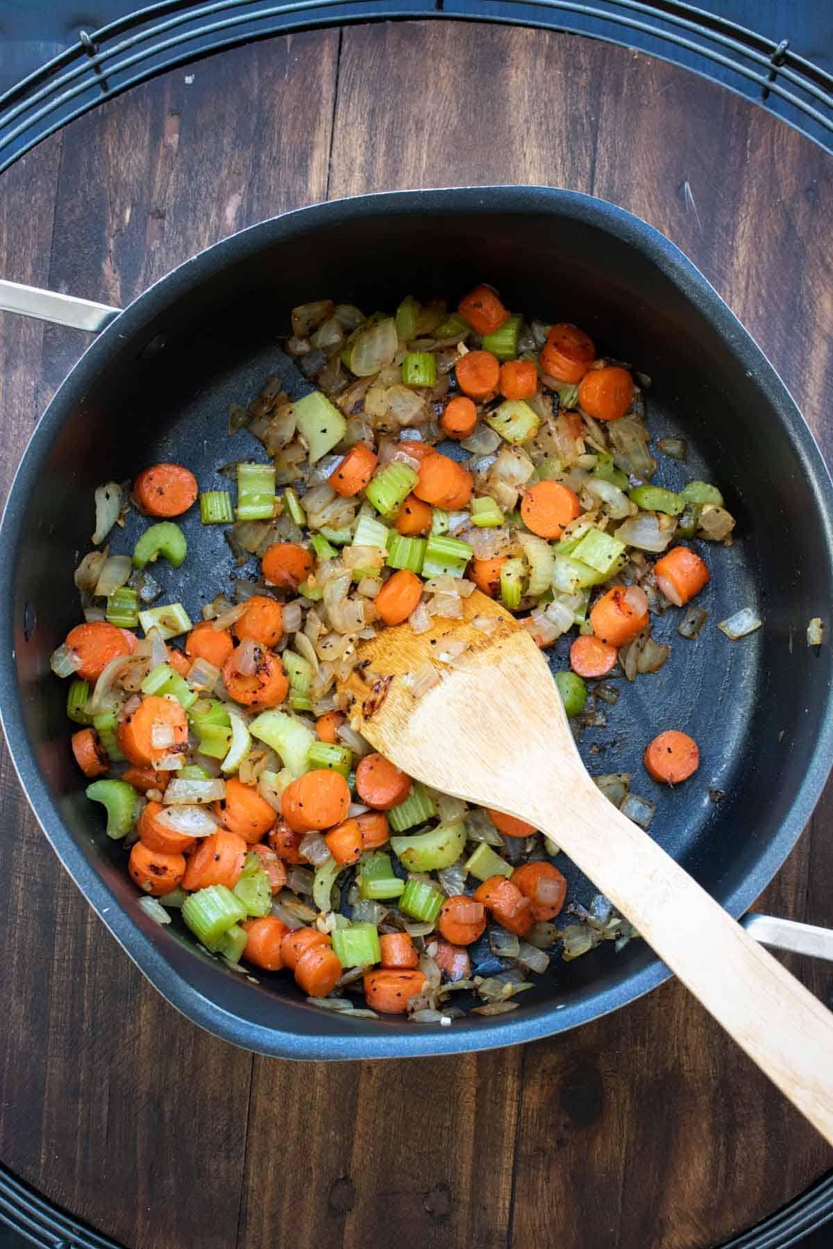 Wooden spoon sautéing veggies in a pot.