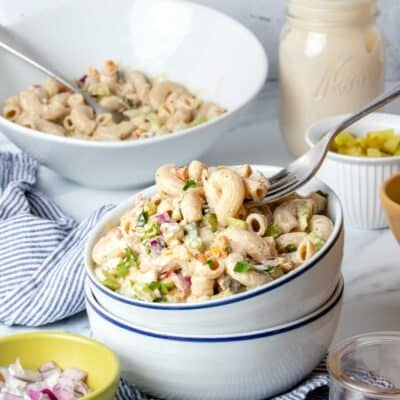 Two white bowls stacked and filled with classic macaroni salad