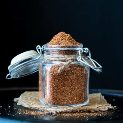 Front view of glass spice jar with clamp lid filled with homemade taco seasoning