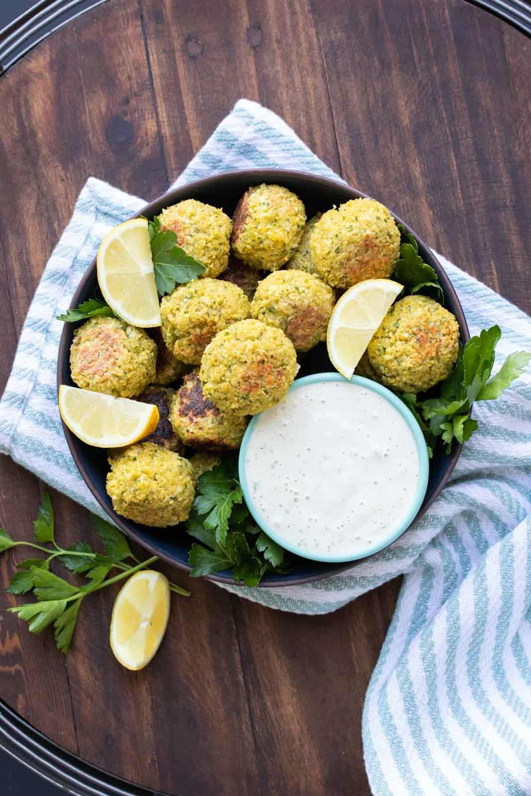 Black bowl filled with baked falafel and tahini dip