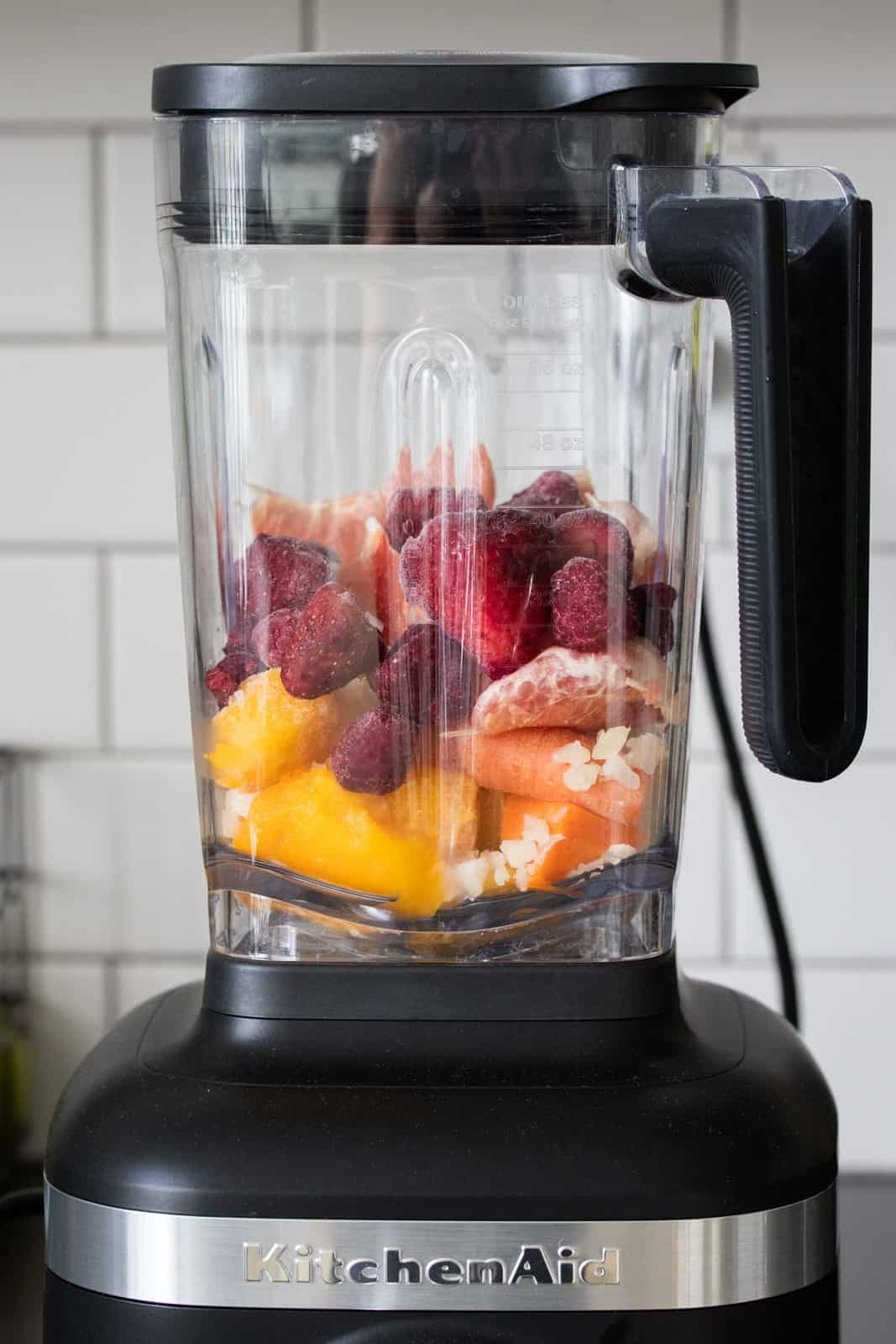 Blender filled with oranges, mango and berries